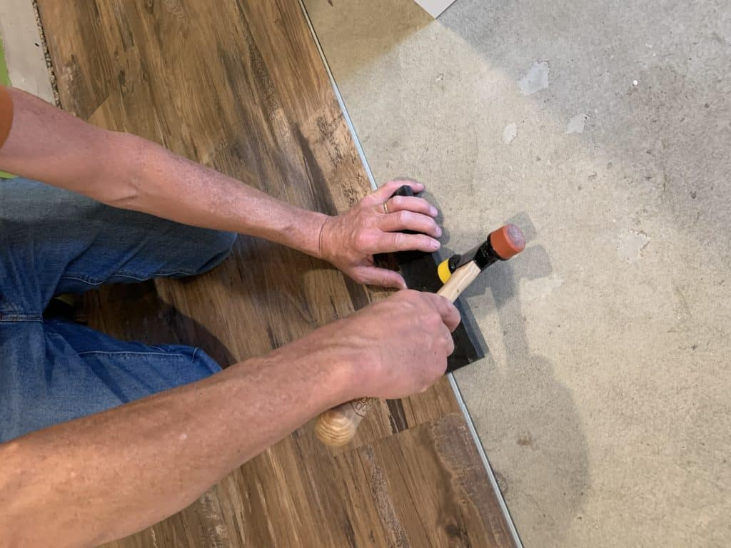 tapping vinyl flooring into place