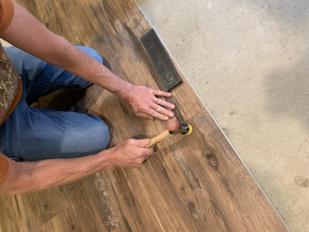 Tapping two vinyl planks together while installing floor