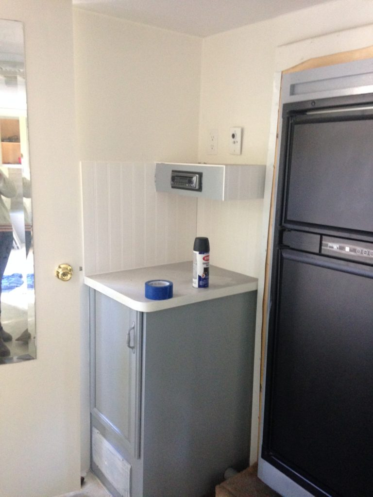 picture of our RV kitchen after painting the fridge and walls. Camper remodel before and after