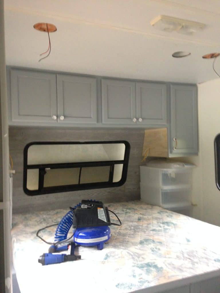 Picture of our RV bedroom after installation of the new cabinets and wood headboard wall